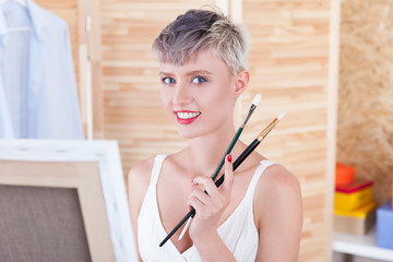 Cheerful artist with two brushes