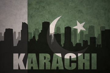 abstract silhouette of the city with text Karachi at the vintage pakistan flag background Fototapete