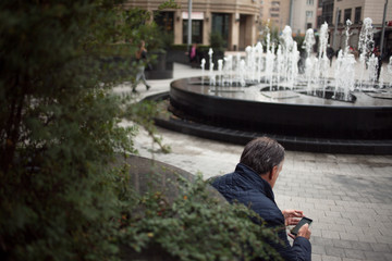 Street scene, man sits on the street with a smartphone