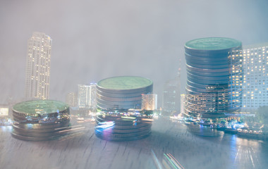 Double exposure city and row of coins, finance and banking concept