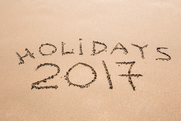 Happy Holidays 2017. Written in sand at the beach. Holiday, Christmas, New Year 2017 concept.