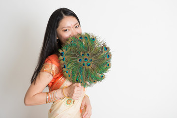 Female with peacock feather fan in Indian sari dress