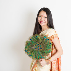 Young girl with peacock feather fan in Indian sari dress