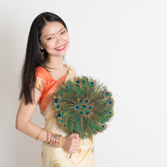 Young female with peacock feather fan in Indian sari dress