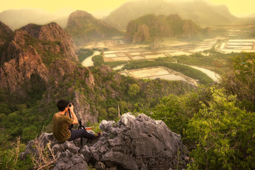 A young man traveler sit on the top of KHAO SAM ROI YOT NATIONAL