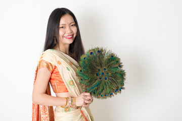 Young woman with peacock feather fan in Indian sari dress