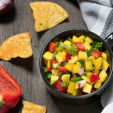 Mango salsa in the bowl and ingredients on the wooden rustic table. Superfoods. Mexican cuisine. Vegetarian concept.