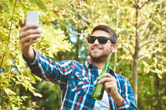 people, leisure and technology concept - close to the man with the smart drinking beer and taking selfie in the park
