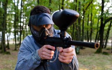 Man shooter with paintball gun wearing protection helmet and dir