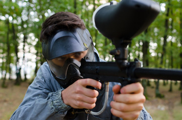 Man attentive with paintball gun wearing protection helmet and d
