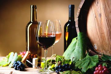 Wine bottles, glasses, grapes and barrel