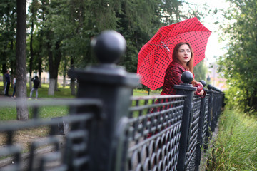 woman with umbrella red on street tree