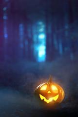 Leuchtender Halloween-Kürbis im nebeligen Wald