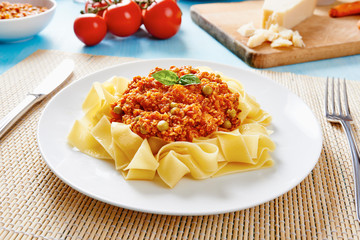 Tagliatelle with Bolognese sauce in white dish surrounded by fresh tomatoes and cheese on blue table