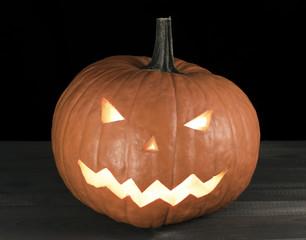 Halloween carved pumpkin, jack-o-lantern on wooden table