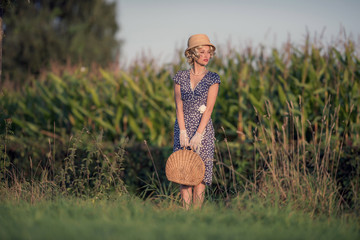 Vintage 1920s summer fashion woman with blue dress and straw hat