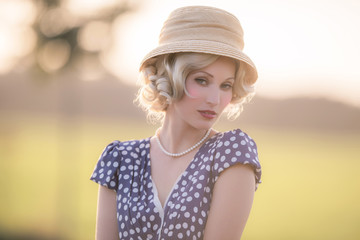 Seductive looking woman wearing vintage 1930s fashion. Standing