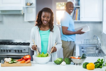 Woman preparing food while man standing in the background