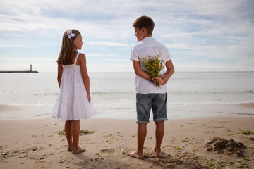 Boy holding flowers behind his back, standing next to girl on beach
