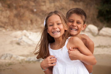 Portrait of a boy and girl on beach hugging and laughing