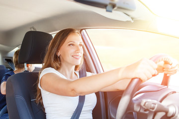 Smiling young woman driving a car at summer day