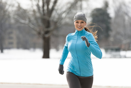 Smiling young woman running through Denver City Park in winter with snowy background