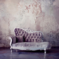 Grunge Styled Interior. Beautiful sofa in classical style on a background of textured walls. Purple toning