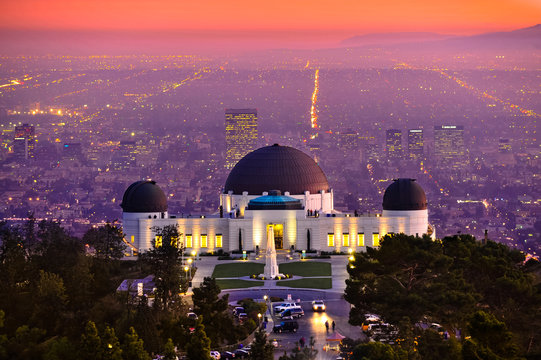Historic famous Griffith Park Observatory at Sunset with Los Angeles city lights sparkling in background and Catalina Island in distance