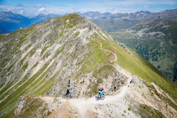 Woman mountain biking in swiss alps near Davos, Graubunden, Switzerland