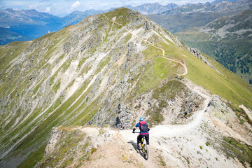 Man mountain biking in swiss alps near Davos, Graubunden, Switzerland