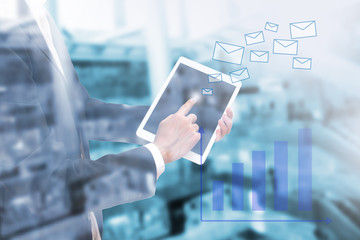 Double exposure of businessman using the tablet to send email with business graph on blur image of building , globalization smart business concept