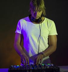 Young and attractive man manipulating a mixer Dj
