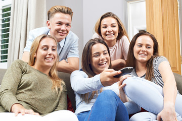 Group Of teenage Friends Watching Television At Home