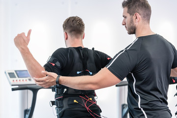 Trainer helping man to do an exercise right in the EMS gym