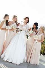 Pretty bridesmaids in peach dresses admire gorgeous bride standi