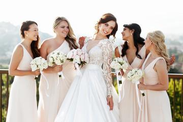 Grogeous dark-haired bride in luxurious dress looks at bridesmai