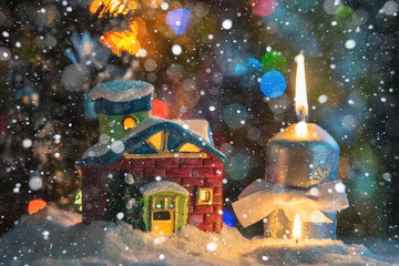 Winter background. Christmas background. Christmas snowman and candles. Close-up. Night Photography.