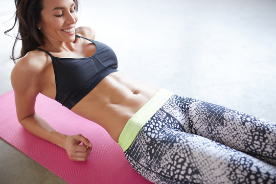 young woman in sports clothing training her abs