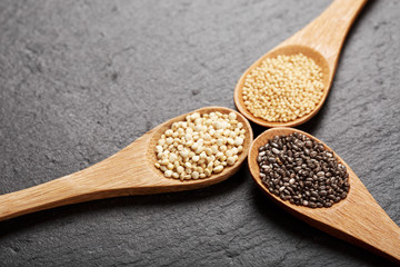 Quinoa, chia and amarantus seeds in wooden spoons