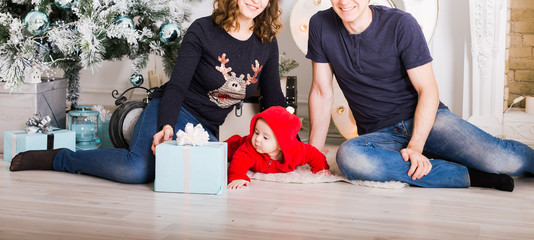 Christmas Family Open Present Gift Box, Mother Father and Baby Child in Decorated Room, sitting under Christmas Tree.