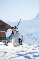 femme souriante qui porte des skis sur l'épaule
