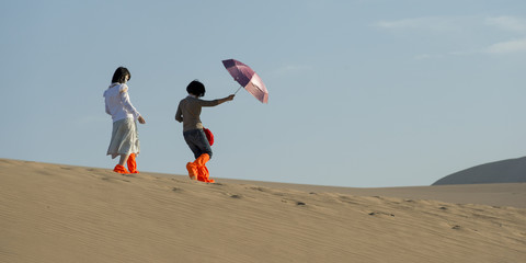 Girls walking on sand dune at Mingsha Shan, Dunhuang, Jiuquan, G