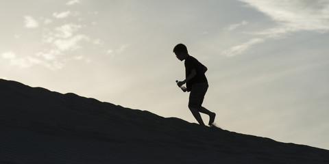 Person climbing on sand dune at Mingsha Shan, Dunhuang, Jiuquan,