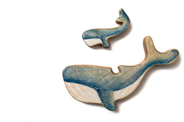 Wooden puzzle in the form of a whale and little whale isolated on white.