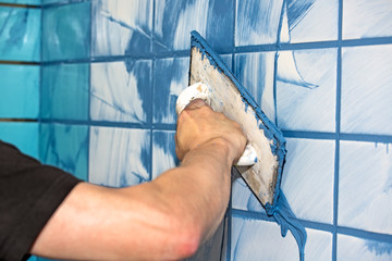 Man applying blue grout to white tiles.