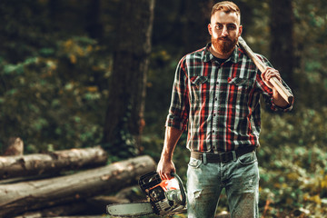 9d086d73f48 Lumberjack worker standing in the forest with axe and chainsaw