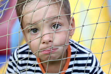 Child face behind net
