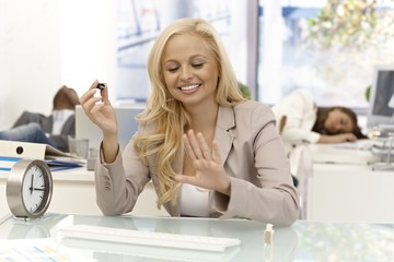 Happy businesswoman polishing nails in office