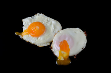 Fried eggs close up on a black background.