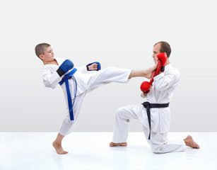 Kicking karateka hits the fitness machine that keeps coach